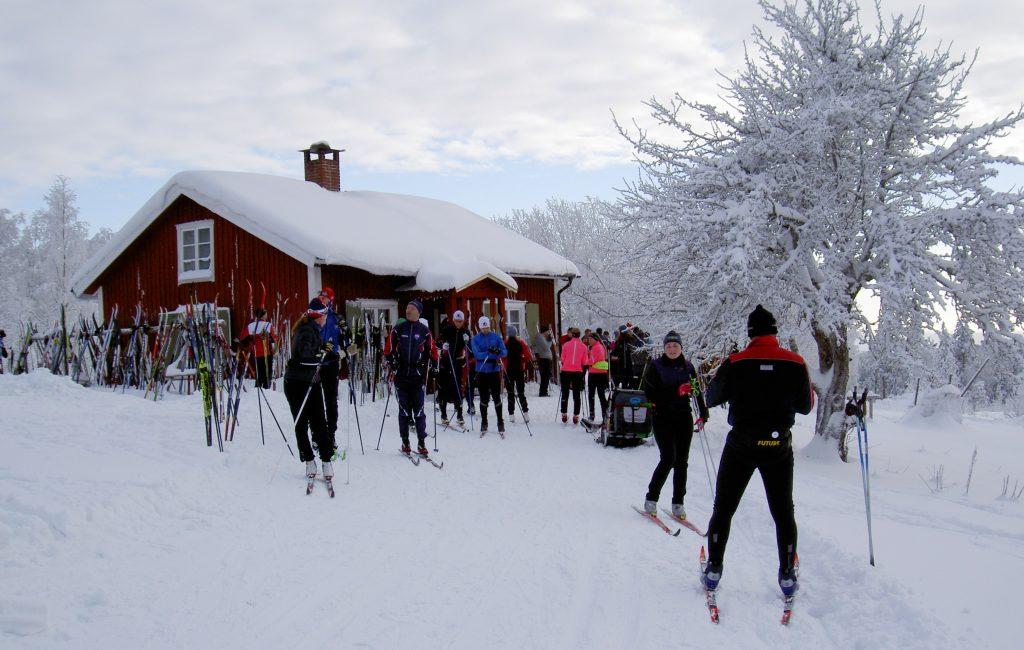 Många skidor vid stugan i snö